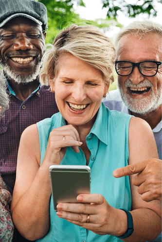 Two older men surrounding an older woman with a smart phone.
