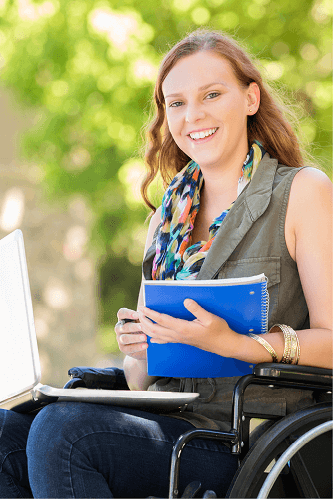 Young woman in a wheelchair with a laptop, outside.