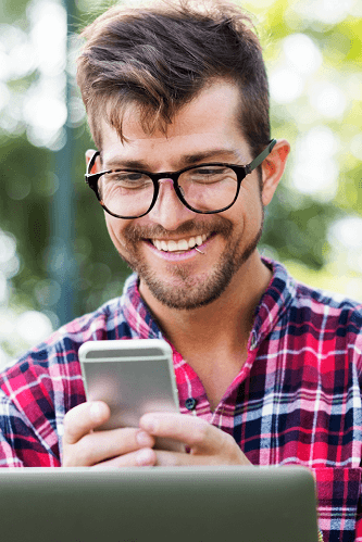 Young man with glasses looking at a smart phone outside.